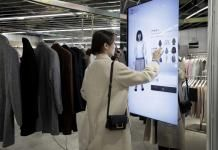 Source: Kiyoshi Ota/Bloomberg. An attendee uses a touch screen to try on clothes on a virtual avatar.